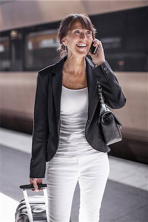 Happy businesswoman using mobile phone on railroad station platform Stock Photo - Premium Royalty-Free, Code: 698-07158665