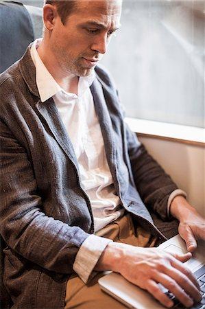 Mature businessman using laptop in train Stock Photo - Premium Royalty-Free, Code: 698-07158663