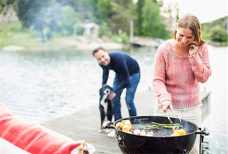 Happy woman using mobile phone while barbecuing with man and dog in background on pier Stock Photo - Premium Royalty-Free, Code: 698-07158688