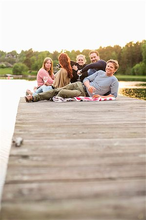 Group of friends relaxing on pier at lake Stock Photo - Premium Royalty-Free, Code: 698-07158701