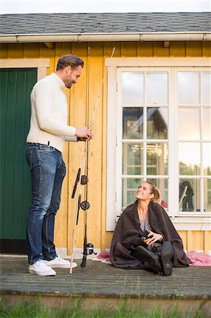 Woman looking at man with fishing rod while sitting at summer house Stock Photo - Premium Royalty-Free, Code: 698-07158702
