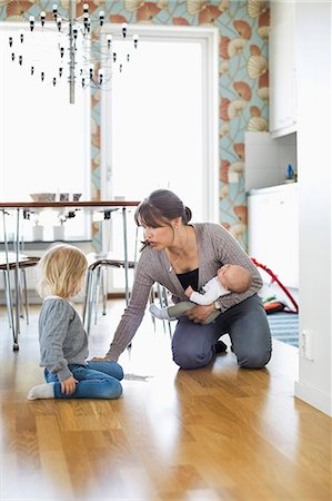 Mother holding baby while cleaning floor with daughter at home Stock Photo - Premium Royalty-Free, Code: 698-07158725