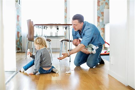 Father holding baby girl while cleaning floor with daughter at home Stock Photo - Premium Royalty-Free, Code: 698-07158728