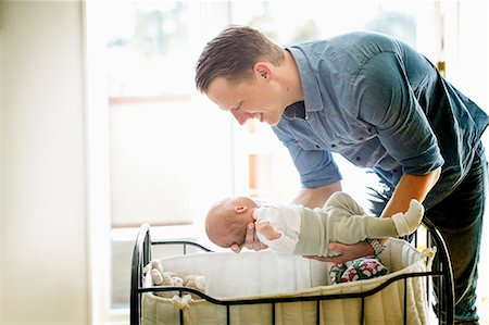Father putting baby girl in cradle at home Stock Photo - Premium Royalty-Free, Code: 698-07158723