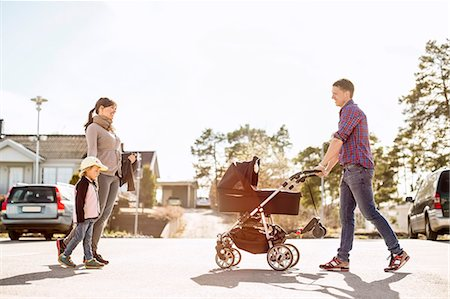 Side view of parents with baby carriage and daughter walking on street Stock Photo - Premium Royalty-Free, Code: 698-07158737