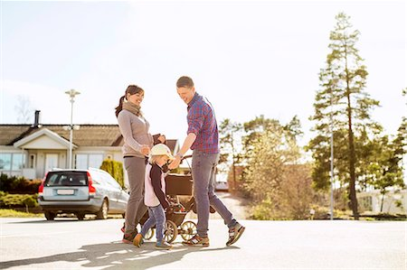 Parents with baby carriage and daughter on street Stock Photo - Premium Royalty-Free, Code: 698-07158738