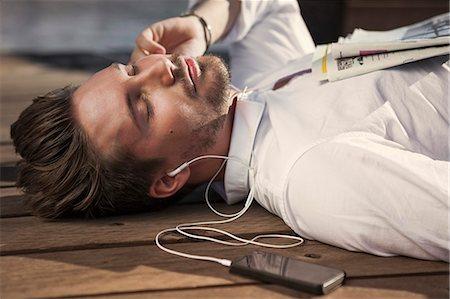 Businessman listening music while lying on boardwalk Stock Photo - Premium Royalty-Free, Code: 698-07158764