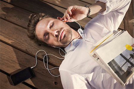 High angle view of businessman listening music while lying on boardwalk Stock Photo - Premium Royalty-Free, Code: 698-07158765
