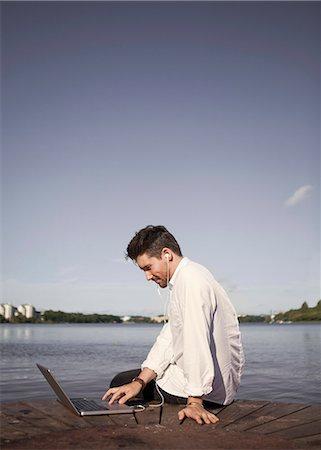 Businessman listening to music while using laptop on boardwalk at seaside Stock Photo - Premium Royalty-Free, Code: 698-07158762