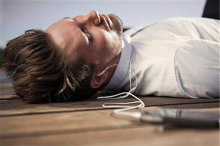 Businessman listening music through mobile phone while lying on boardwalk Stock Photo - Premium Royalty-Free, Code: 698-07158763