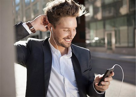 Young businessman smiling while listening music through mobile phone on street Stock Photo - Premium Royalty-Free, Code: 698-07158774