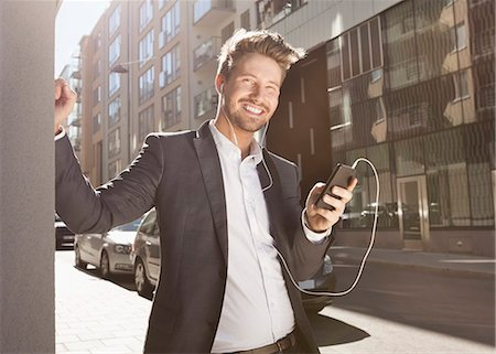 Happy young businessman listening music through mobile phone on street Stock Photo - Premium Royalty-Free, Code: 698-07158775