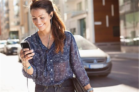 Happy businesswoman using mobile phone while listening music on street Stock Photo - Premium Royalty-Free, Code: 698-07158776