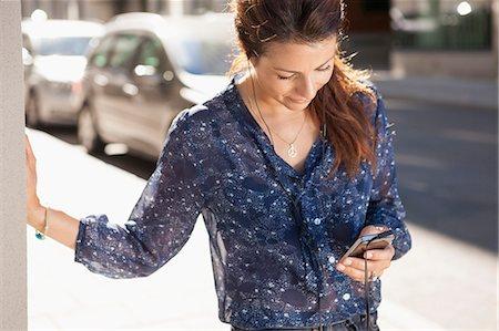 Businesswoman using mobile phone on street Stock Photo - Premium Royalty-Free, Code: 698-07158777