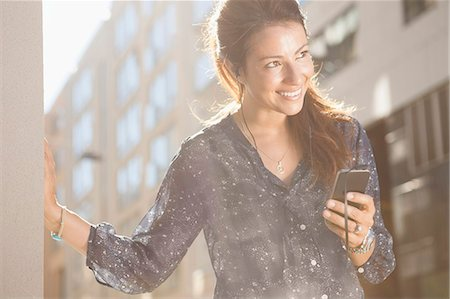 Happy businesswoman looking away while listening music through mobile phone outdoors Stock Photo - Premium Royalty-Free, Code: 698-07158778