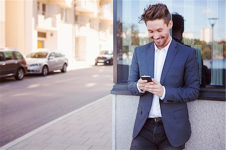 Young businessman using mobile phone against wall by sidewalk Stock Photo - Premium Royalty-Free, Code: 698-07158779