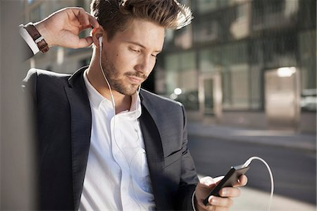 Young businessman listening music through mobile phone outdoors Stock Photo - Premium Royalty-Free, Code: 698-07158773