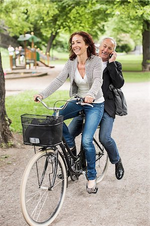 Happy businesswoman riding bicycle while colleague using mobile phone on back seat Stock Photo - Premium Royalty-Free, Code: 698-07158814