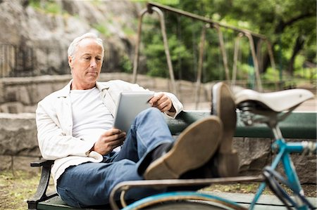 Businessman with feet up on bicycle using digital tablet on park bench Stock Photo - Premium Royalty-Free, Code: 698-07158819