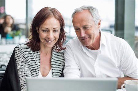 Happy business people using laptop at cafe Stock Photo - Premium Royalty-Free, Code: 698-07158839