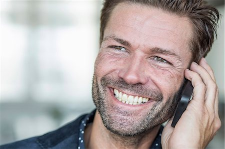 Close-up of happy businessman using mobile phone Stock Photo - Premium Royalty-Free, Code: 698-07158877