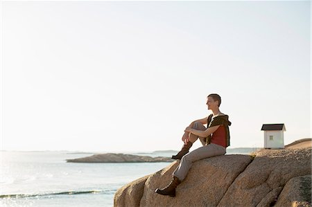Full length of woman relaxing on rock at seaside Stock Photo - Premium Royalty-Free, Code: 698-07439339
