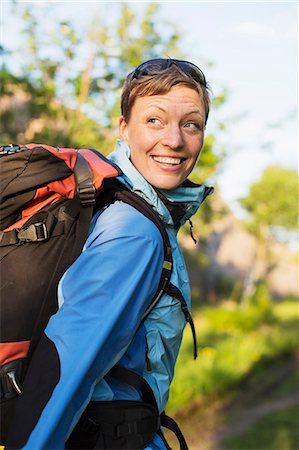 Female hiker with backpack looking over shoulder outdoors Stock Photo - Premium Royalty-Free, Code: 698-07439344