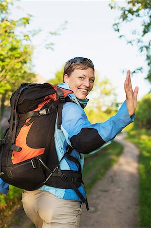 Portrait of happy female backpacker waving while hiking at forest Stock Photo - Premium Royalty-Free, Code: 698-07439345