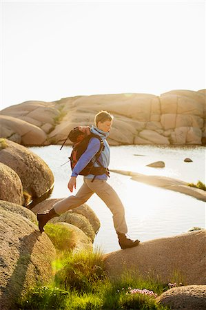 Side view of female backpacker hiking on rocks Stock Photo - Premium Royalty-Free, Code: 698-07439341