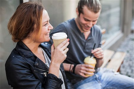 Happy woman drinking coffee in disposable cup with man on bench at sidewalk Stock Photo - Premium Royalty-Free, Code: 698-07439374