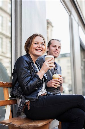 Happy couple drinking coffee in disposable cups on bench at sidewalk Stock Photo - Premium Royalty-Free, Code: 698-07439375