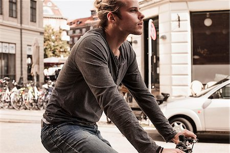 Side view of young man cycling on city street Stock Photo - Premium Royalty-Free, Code: 698-07439383
