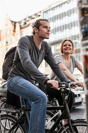 Man and woman cycling on city street Stock Photo - Premium Royalty-Free, Code: 698-07439396