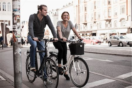 Happy couple riding bicycles on city street Stock Photo - Premium Royalty-Free, Code: 698-07439392