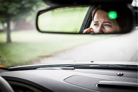 Reflection of woman in rear-view mirror of car Stock Photo - Premium Royalty-Free, Code: 698-07439460