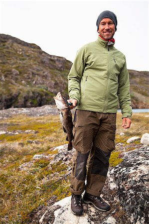Full length portrait of mature man in warm clothing holding fish outdoors Stock Photo - Premium Royalty-Free, Code: 698-07439479
