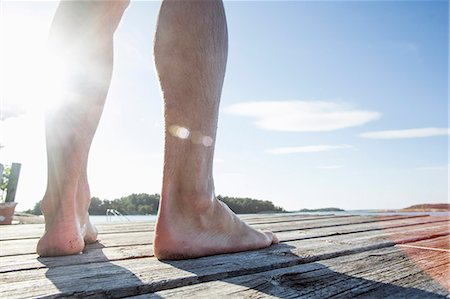 Low section of mature man standing on boardwalk Stock Photo - Premium Royalty-Free, Code: 698-07439512