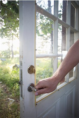 Cropped image of man holding door handle Stock Photo - Premium Royalty-Free, Code: 698-07439524