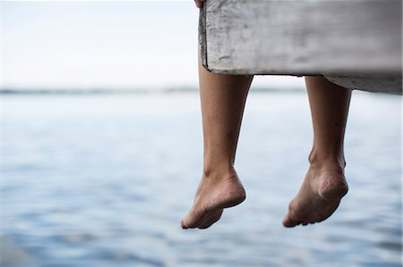 dangling - Low section of woman dangling feet from pier Stock Photo - Premium Royalty-Free, Code: 698-07439528