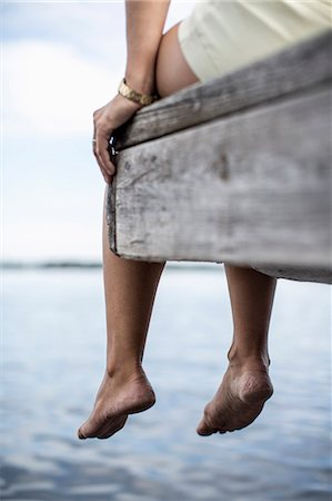 dangling - Low section of woman dangling feet from pier Stock Photo - Premium Royalty-Free, Code: 698-07439529