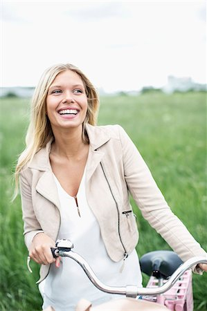 Happy young woman with bicycle looking away while standing at field Stock Photo - Premium Royalty-Free, Code: 698-07439531