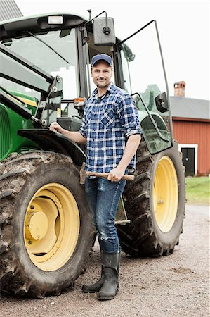 Full length portrait of farmer with hammer standing by tractor on farm Stock Photo - Premium Royalty-Free, Code: 698-07439548
