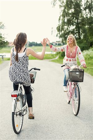 friend (female) - Happy female friends giving high five while cycling on country road Stock Photo - Premium Royalty-Free, Code: 698-07439542