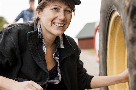 farmhand (female) - Portrait of smiling female farmer repairing tractor wheel Stock Photo - Premium Royalty-Free, Code: 698-07439554