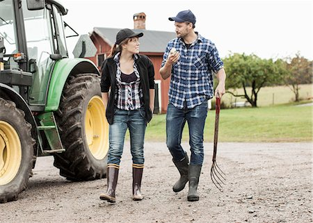 Full length of farming couple walking by tractor Stock Photo - Premium Royalty-Free, Code: 698-07439557