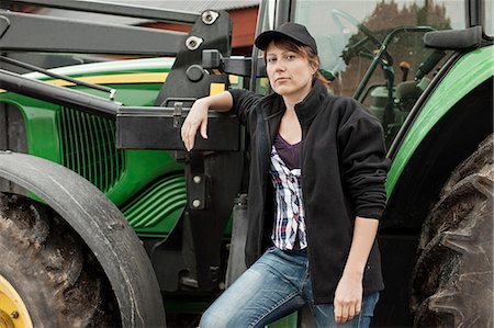 farmhand (female) - Portrait of confident female farmer standing by tractor Stock Photo - Premium Royalty-Free, Code: 698-07439552