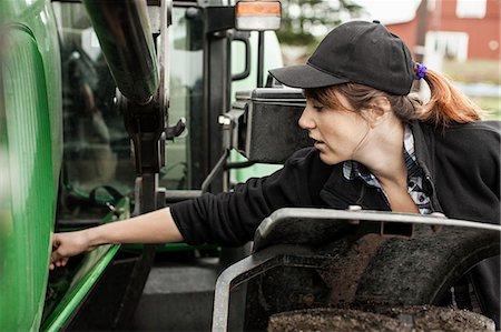 farmhand (female) - Female farmer repairing tractor Stock Photo - Premium Royalty-Free, Code: 698-07439553