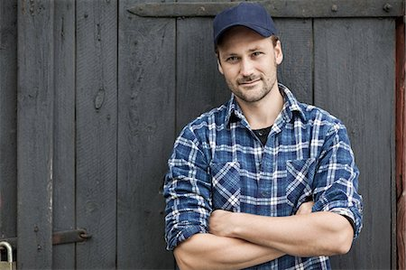 Portrait of confident farmer standing arms crossed against barn door Stock Photo - Premium Royalty-Free, Code: 698-07439568