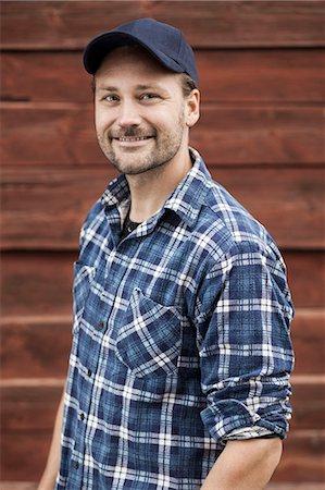 Portrait of confident farmer smiling against barn Stock Photo - Premium Royalty-Free, Code: 698-07439569