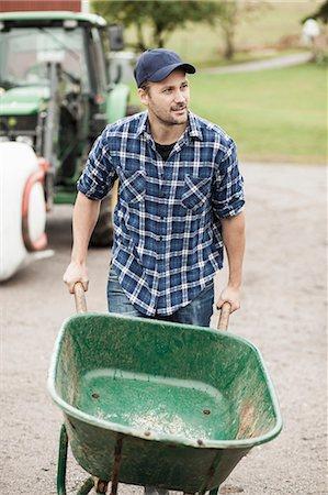 Mid adult farmer pushing wheelbarrow on rural road Stock Photo - Premium Royalty-Free, Code: 698-07439560
